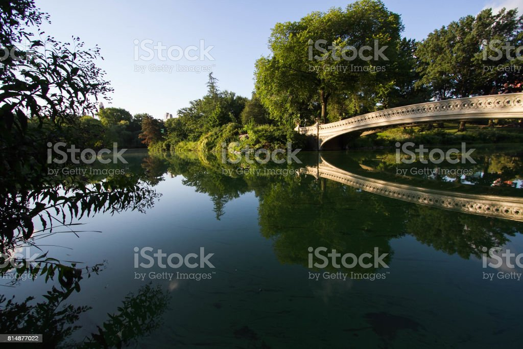 Bow bridge reflects on the clearly lake at Central Park in morning light stock photo