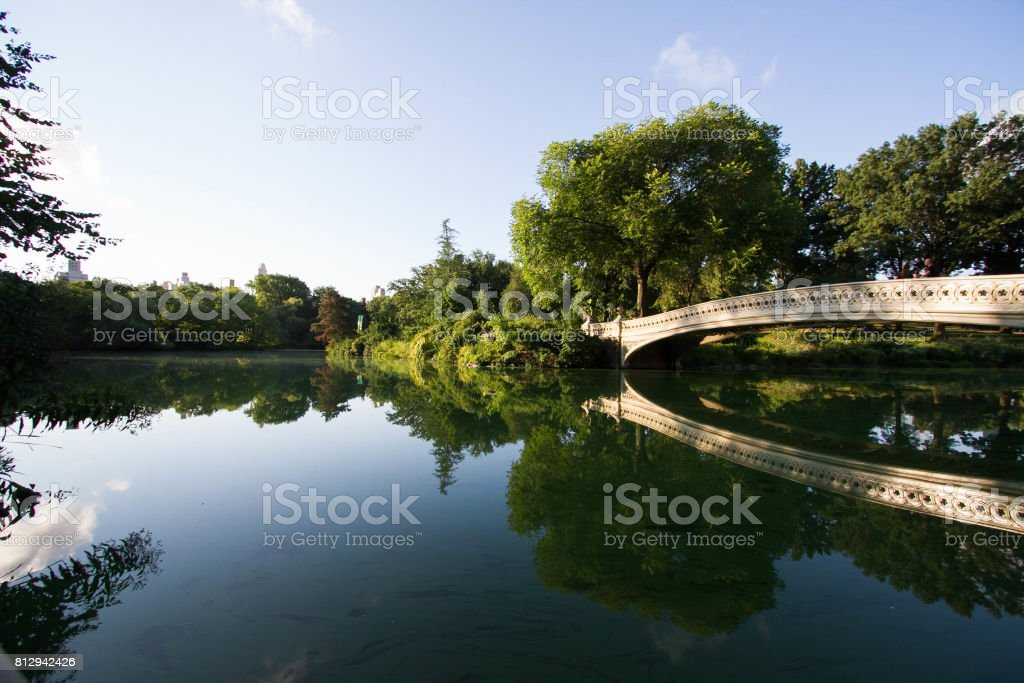 Bow bridge reflects on the lake at Central Park in morning light and shadow stock photo