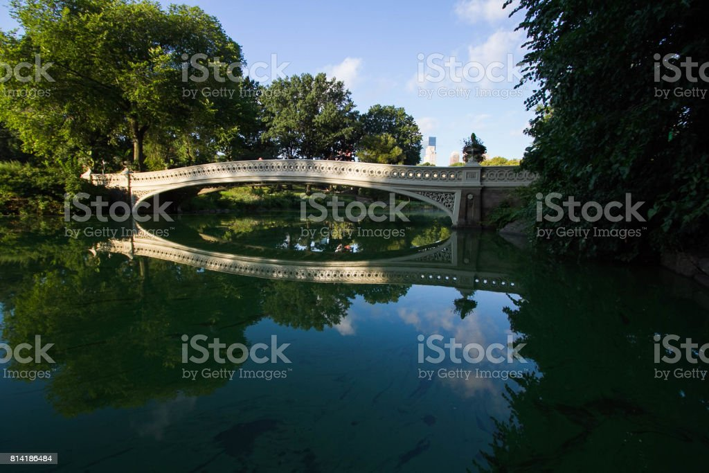 Bow bridge reflects on the lake at Central Park in morning light and cloud stock photo