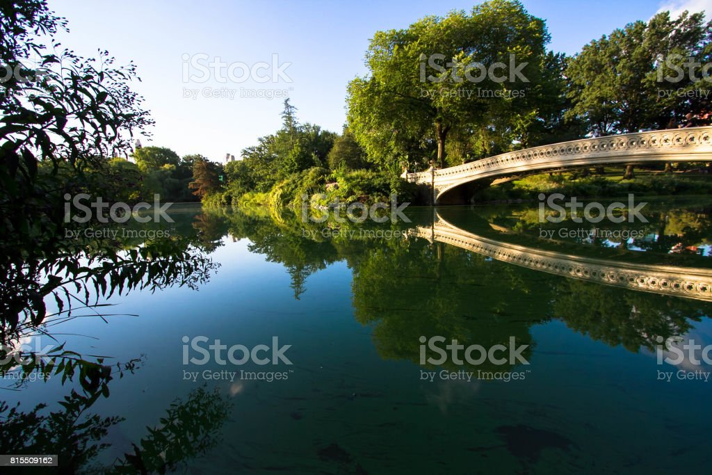 Bow bridge reflects on the lake at Central Park in morning light stock photo