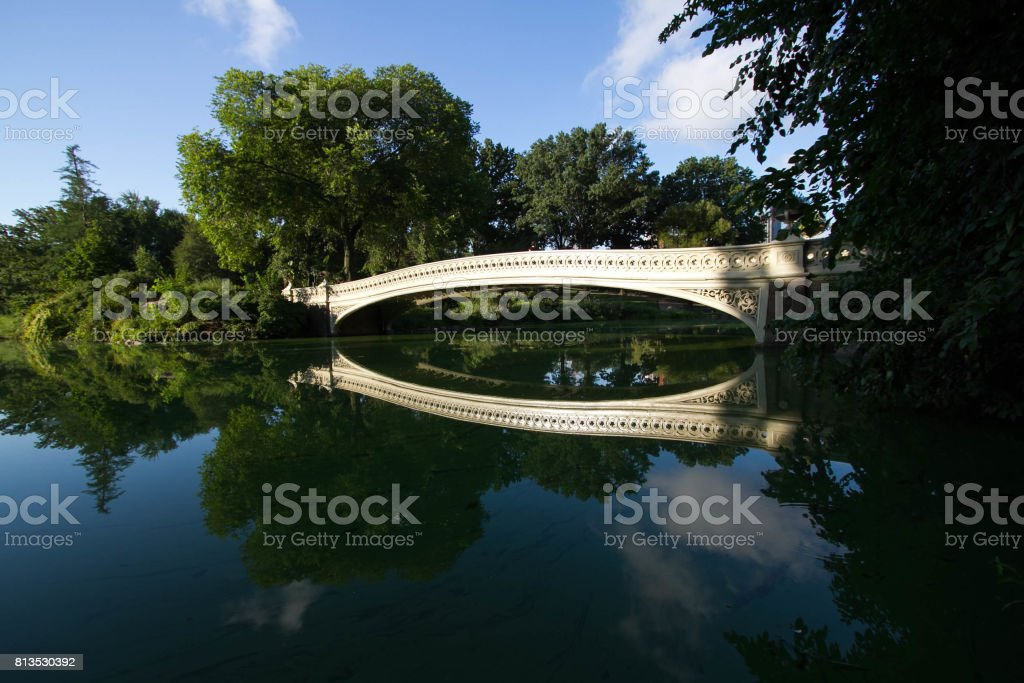 Bow bridge, trees under the shade and blue sky reflect on calming water at Central Park stock photo