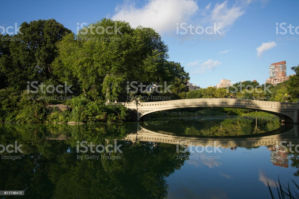 Bow bridge with shade and big trees reflect in lake with cloudy sky at Central Park stock photo