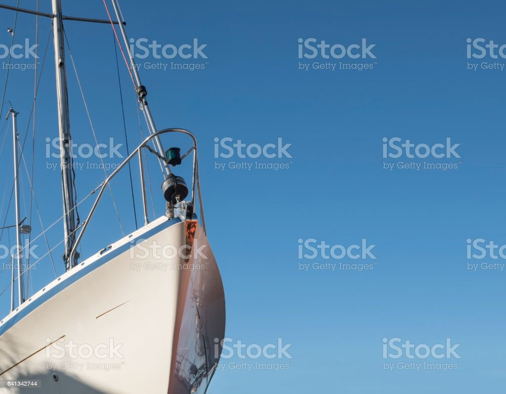 Bow of a white sailing yacht, blue sky, copy space stock photo
