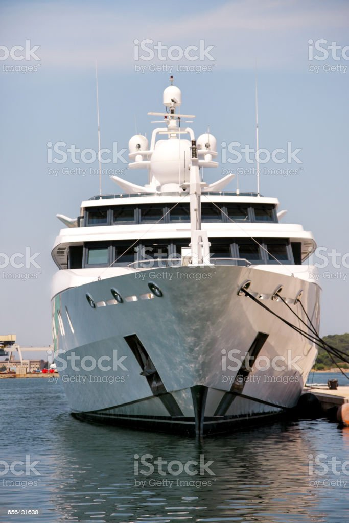 Bow of large modern luxury white yacht and ship anchored in harbor. Large white modern motorboat super yacht and ship in the port city of Pula, Croatia. Yachting concept. stock photo