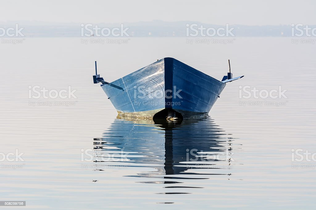 Bow of the boat is reflected in the water stock photo