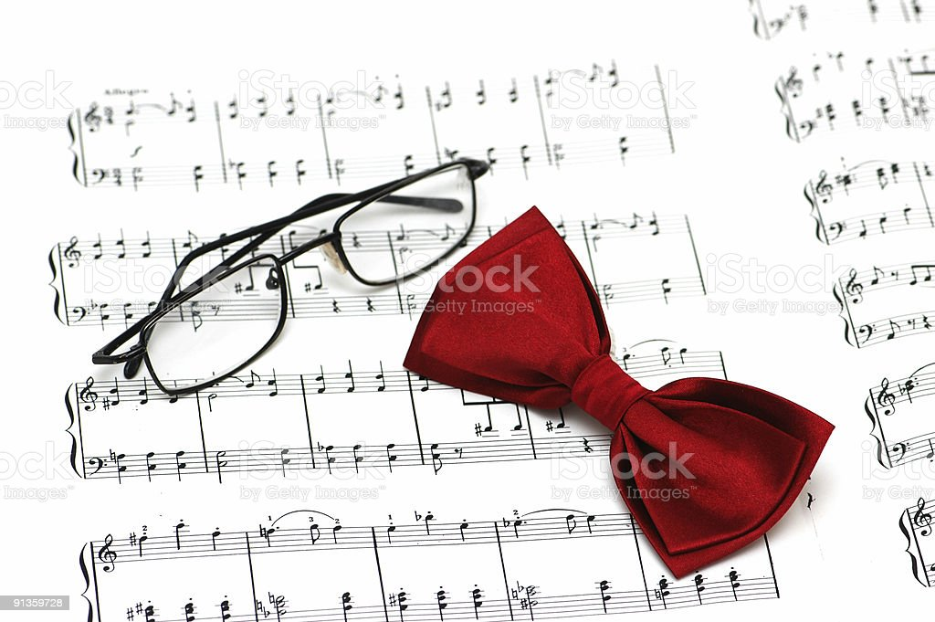 Bow tie and reading glasses on note paper stock photo