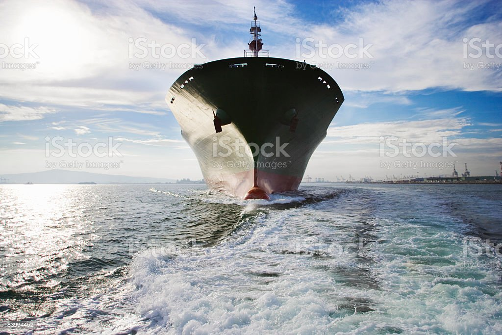 Bow view of cargo ship sailing out of port. stock photo