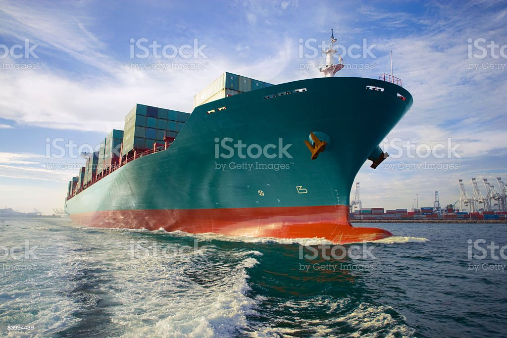Bow view of loaded cargo ship sailing out of port. stock photo