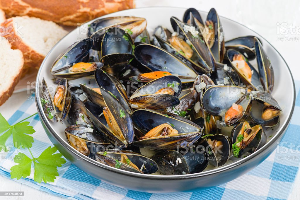 Bowl containing moules marinieres on a blue and white cloth stock photo