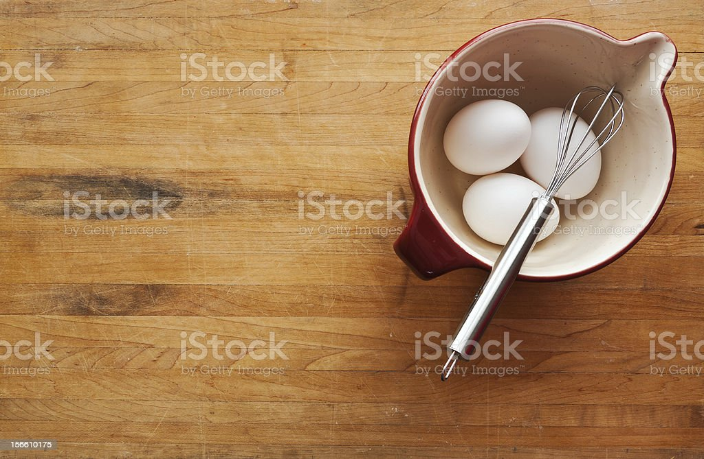 Bowl filled with eggs and whisk on butcher block counter stock photo
