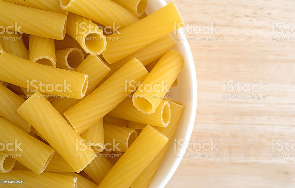 Bowl filled with rigatoni pasta on wood table stock photo