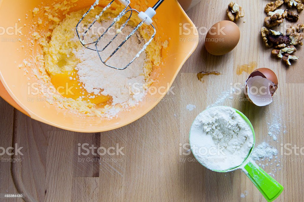 Bowl, flour, eggs and nuts on the wood desk. stock photo