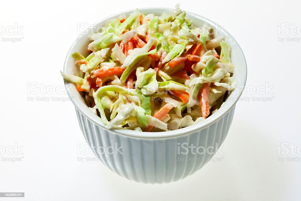 A bowl full of coleslaw on a white background stock photo