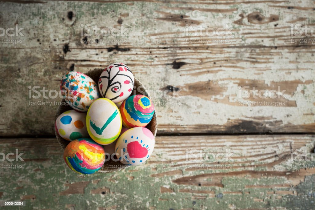 A Bowl full of colorful Easter eggs on a rustic table stock photo