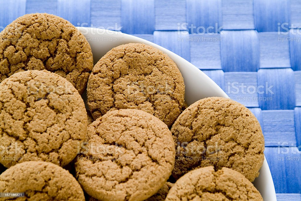 Bowl full of ginger snaps on blue tablecloth stock photo