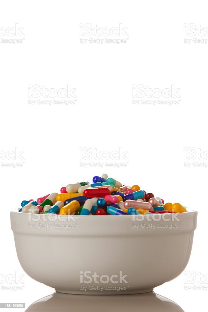 Bowl full of medications, capsules, and pills. stock photo