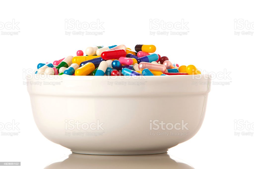 Bowl full of pills, capsules and other medications. stock photo