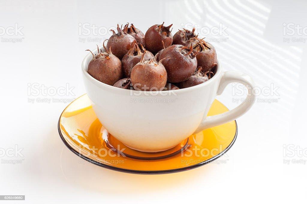 bowl full of ripe medlar on a white background stock photo