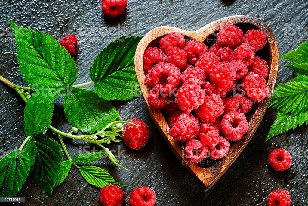 Bowl in the shape of a heart with fresh raspberries stock photo