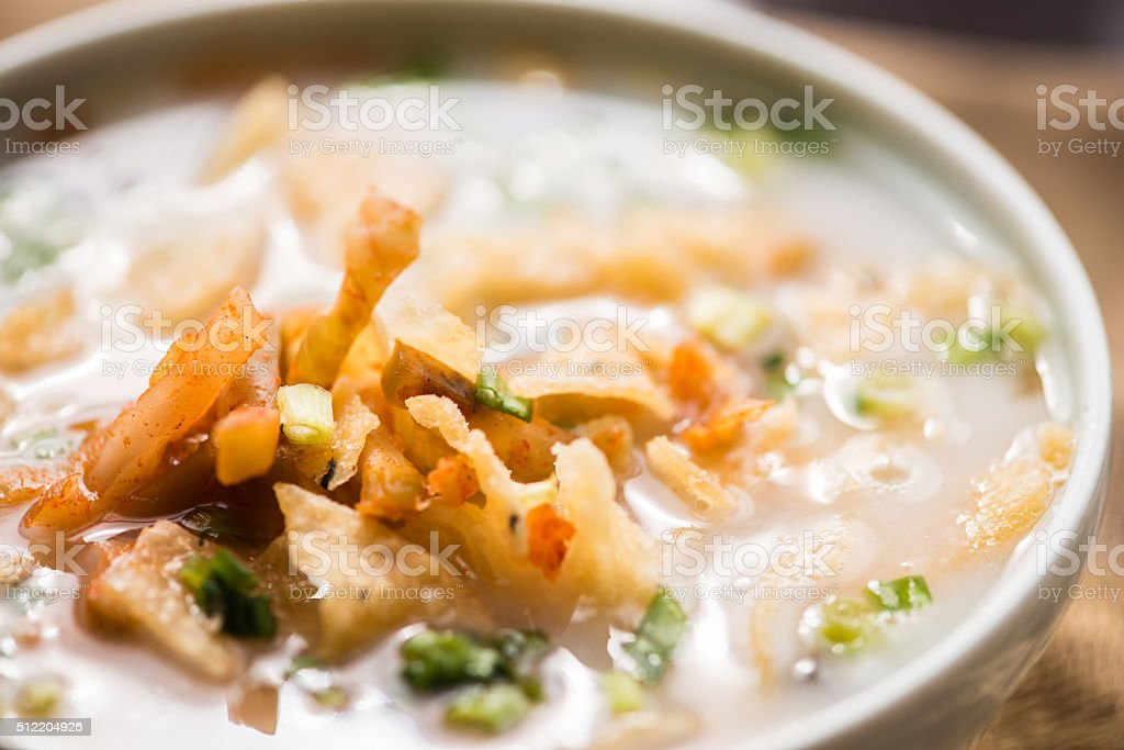 Bowl of Asian Congee, Rice Porridge, Gruel with Garnishes stock photo