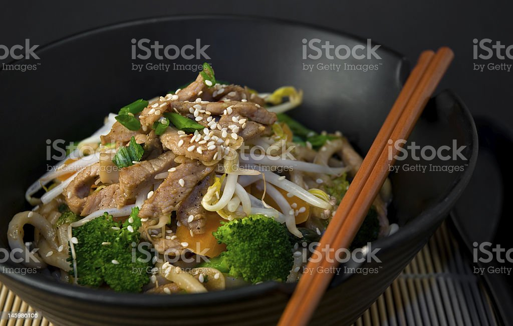 A bowl of Asian stir fry with chopsticks stock photo