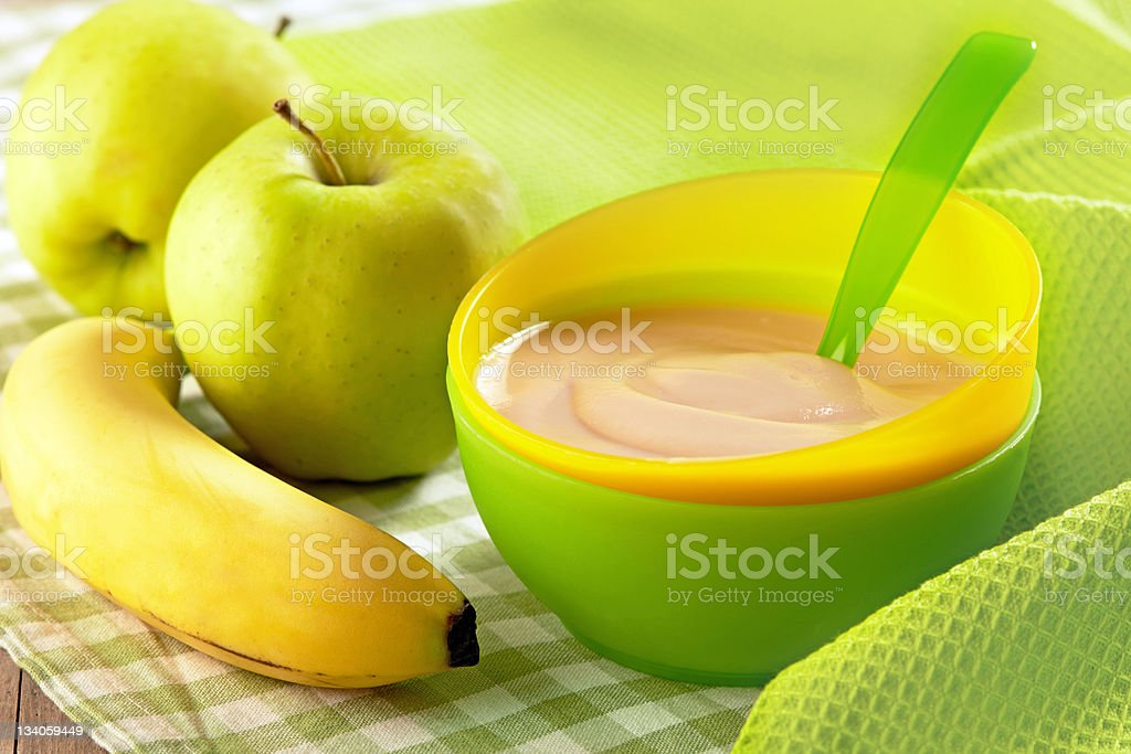 A bowl of baby food with a banana royalty-free stock photo