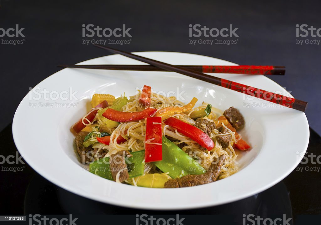 Bowl of beef and vegetable stirfry with vermicelli and chopsticks royalty-free stock photo