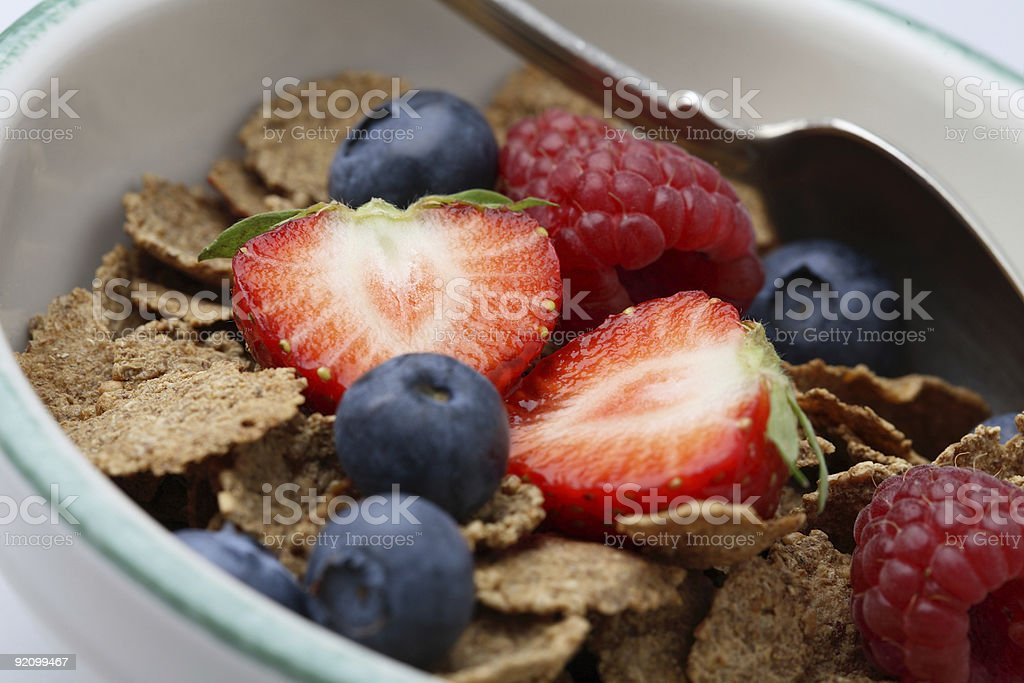 Bowl of breakfast cereal with fruit and a spoon. royalty-free stock photo