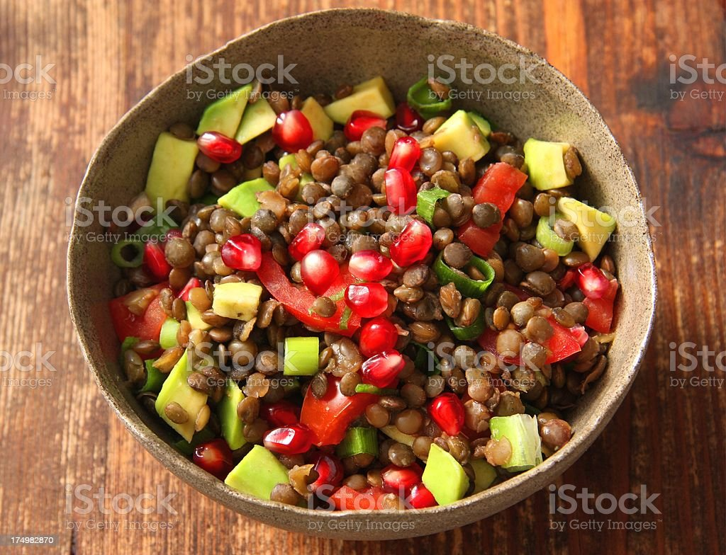 Bowl of brown lentil salad sitting on a wooden table top stock photo