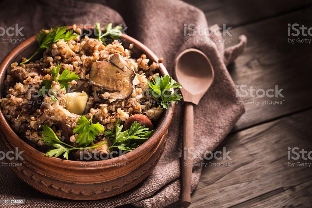 Bowl of buckwheat porridge with mushrooms stock photo