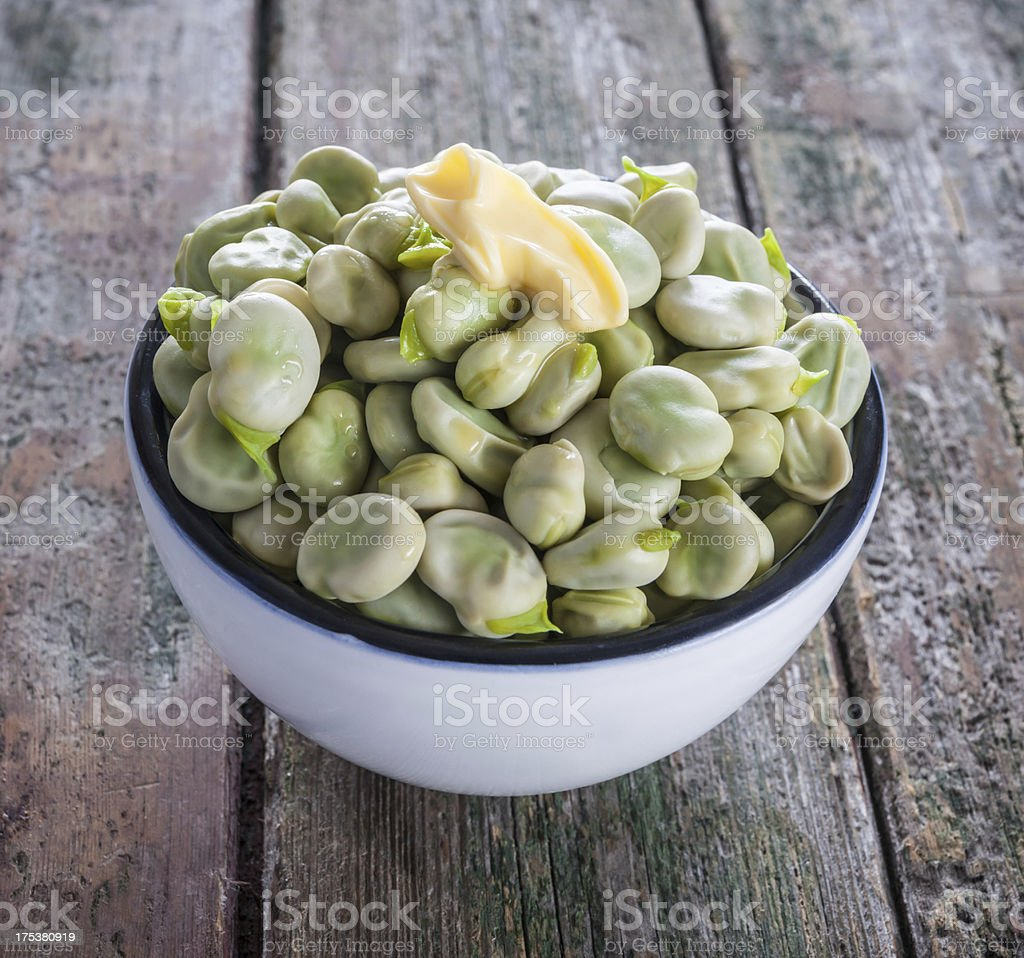 Bowl of buttered broad beans on rustic wood surface closeup stock photo