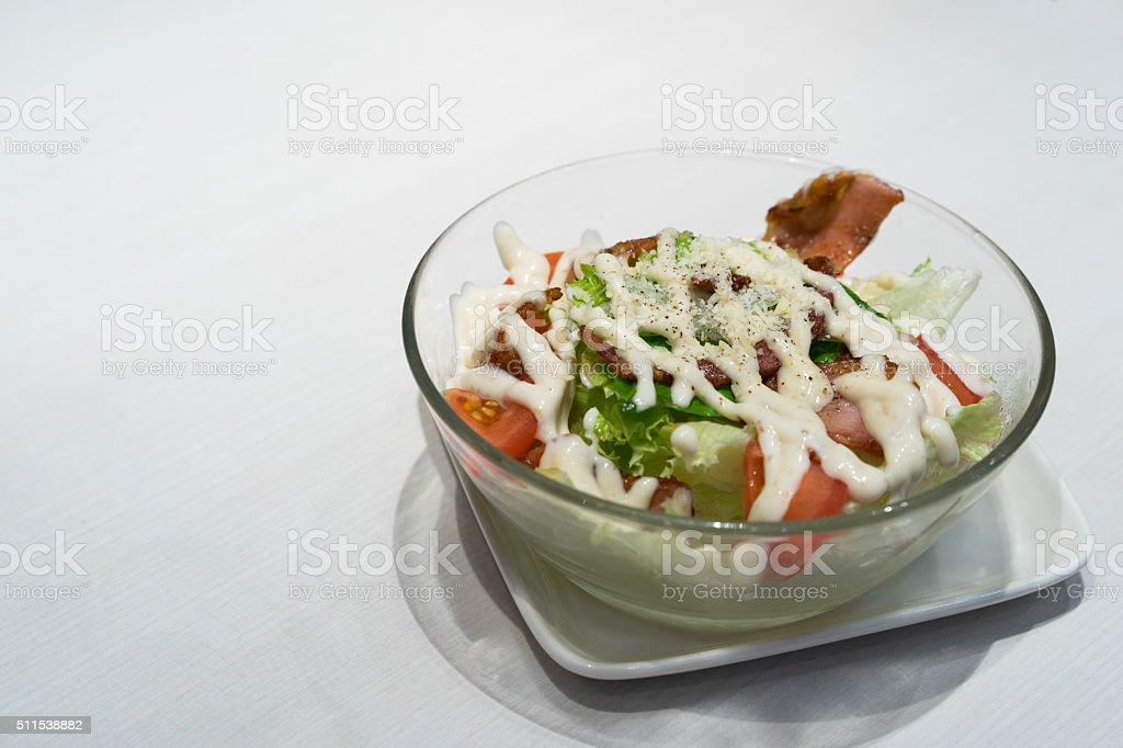 Bowl of caesar salad with bacon on white table stock photo