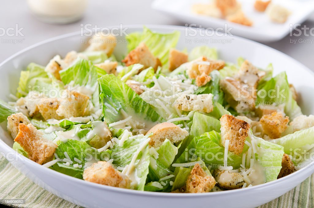 A bowl of Caesar Salad with croutons and cheese on table royalty-free stock photo