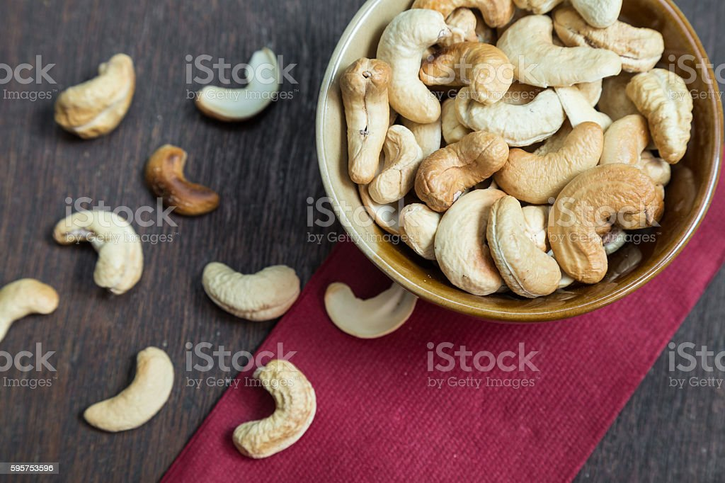 Bowl of cashew nuts from above. On wood background. stock photo
