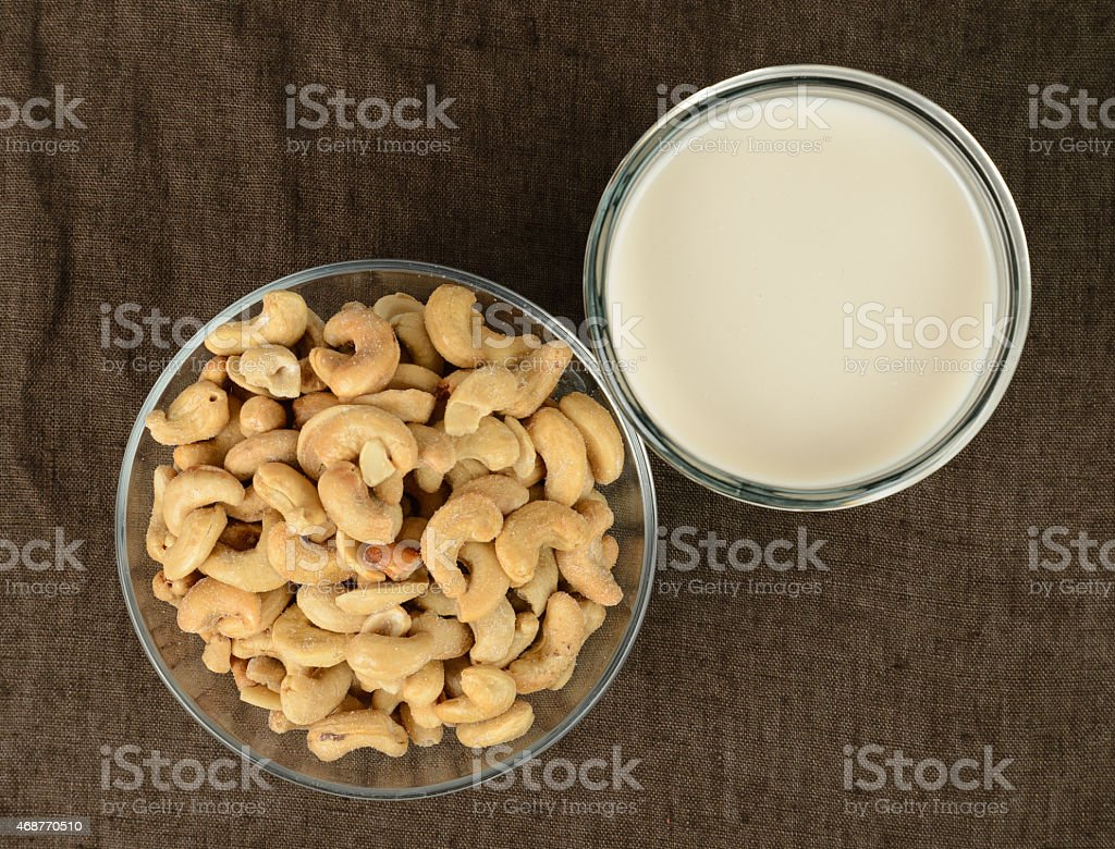 A bowl of cashews and a glass of milk stock photo