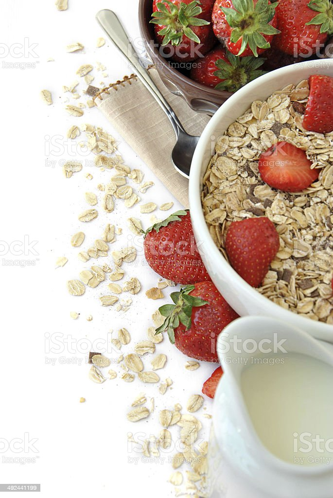 bowl of cereal with milk and strawberries stock photo