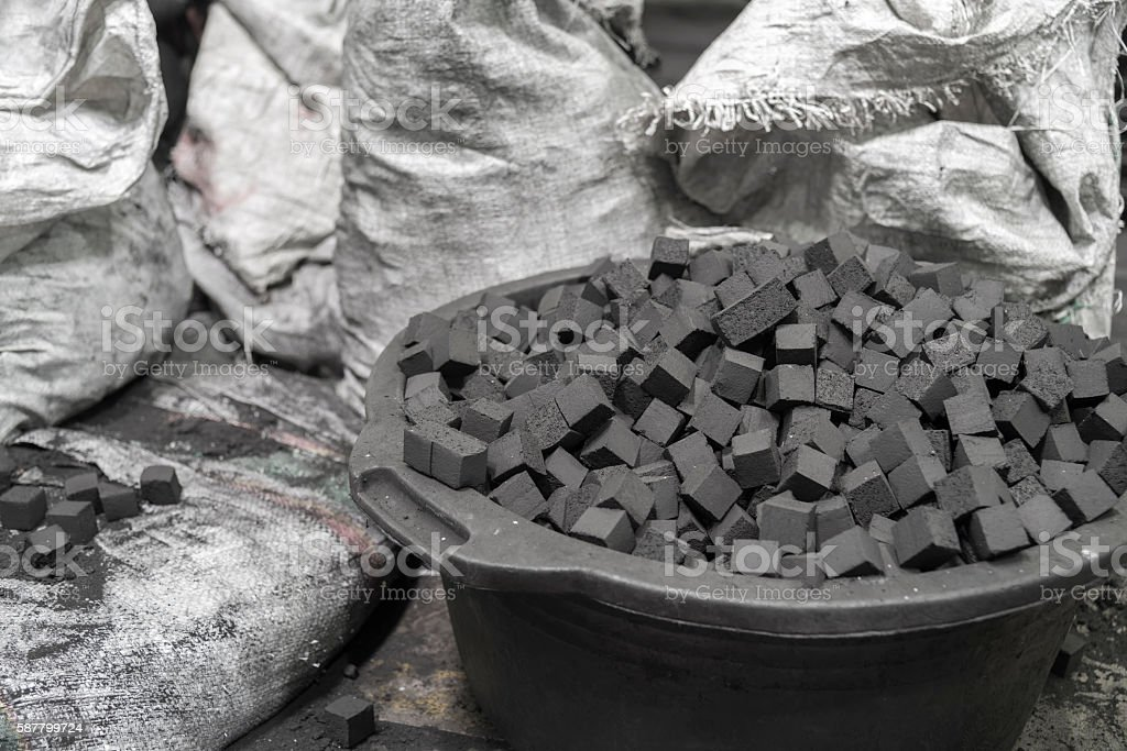 Bowl of charcoal cubes for hookah stock photo