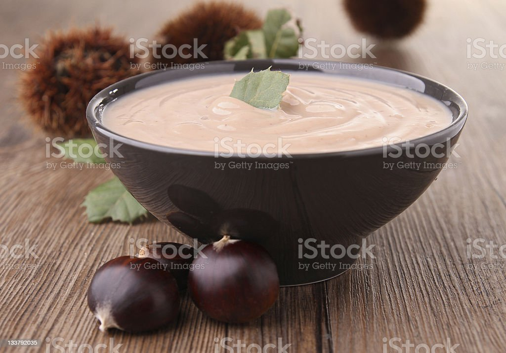 A bowl of chestnut soup on a wooden surface royalty-free stock photo