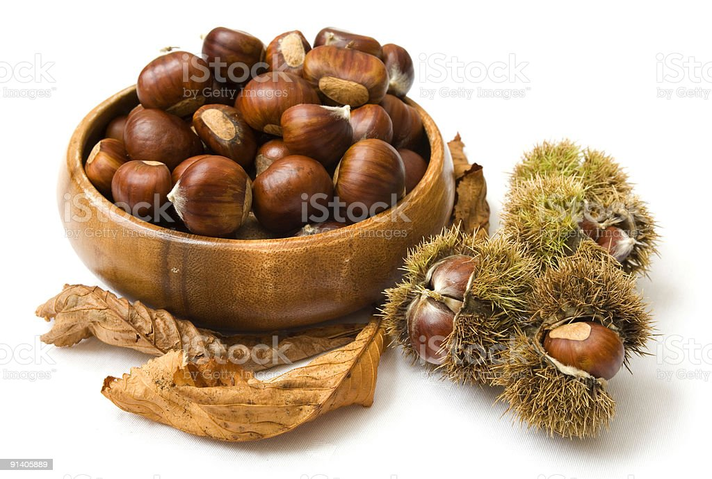 Bowl of chestnuts around leaves stock photo