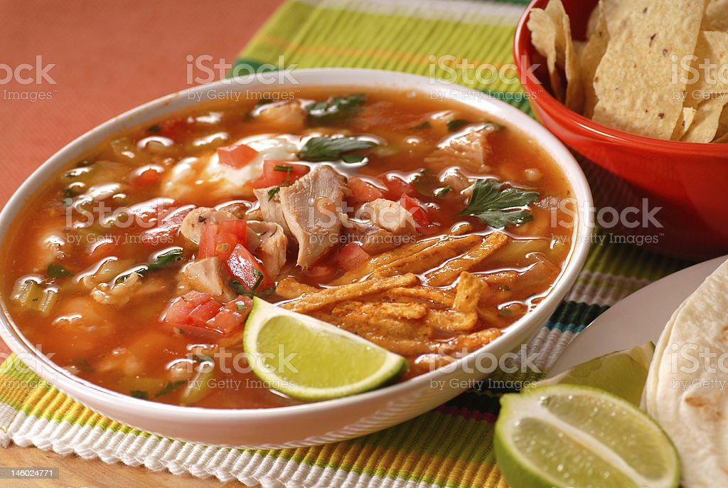 Bowl of chicken and tortilla soup with lime stock photo