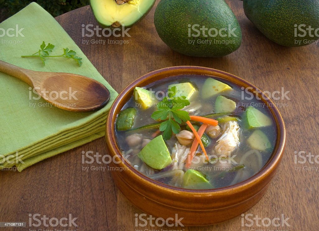 Bowl of Chicken & Avocado Vegetable Soup Lunch on Dining Table royalty-free stock photo