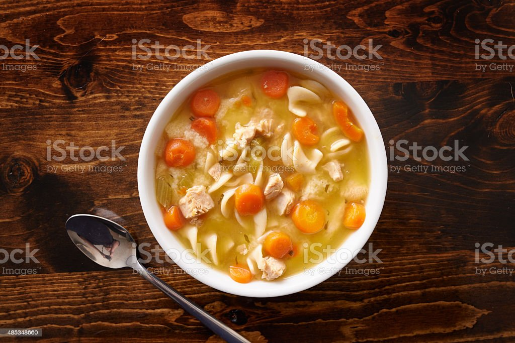 bowl of chicken noodle soup shot top down stock photo