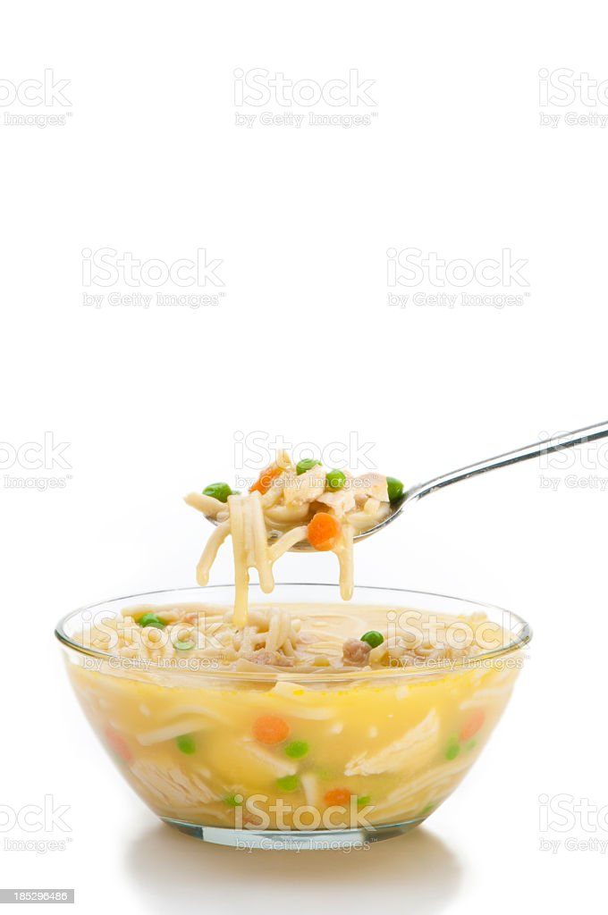 Bowl of chicken noodle soup with spoon on white background stock photo