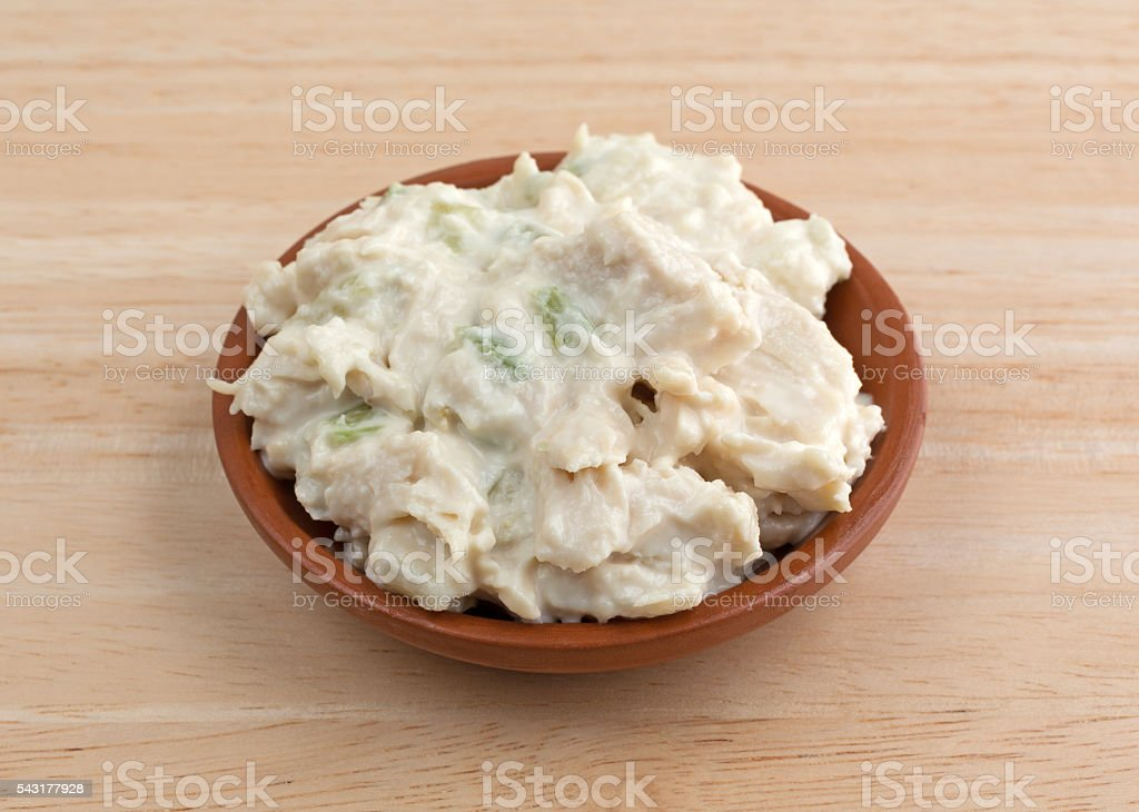 Bowl of chicken salad on a wood table stock photo