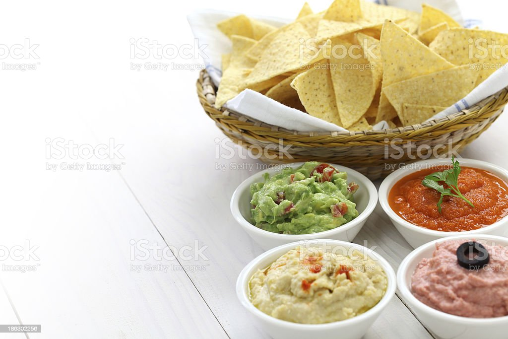 Bowl of chips next to dips for the Super Bowl on white table stock photo