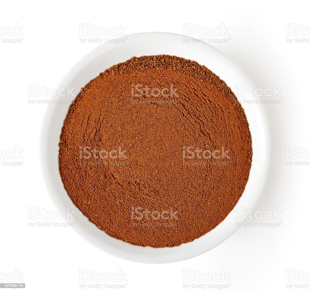 bowl of cinnamon powder isolated on white, from above stock photo