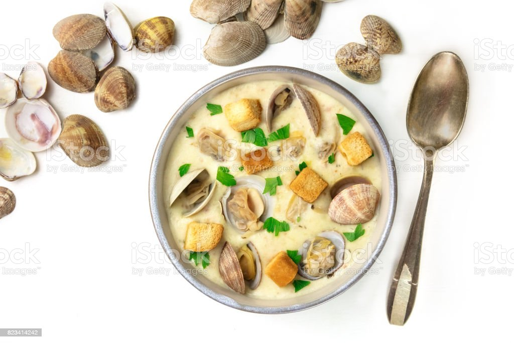 Bowl of clam chowder soup with shells on white background stock photo