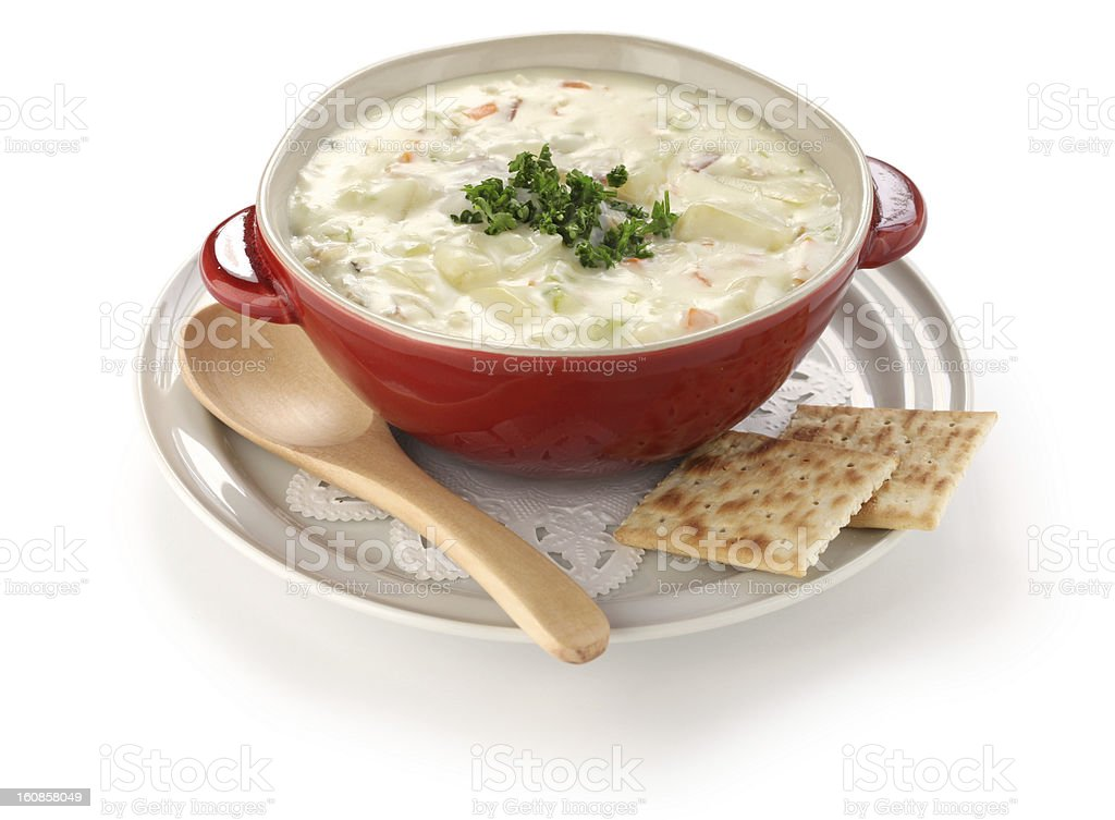 A bowl of clam chowder with a spoon and two saltine crackers stock photo