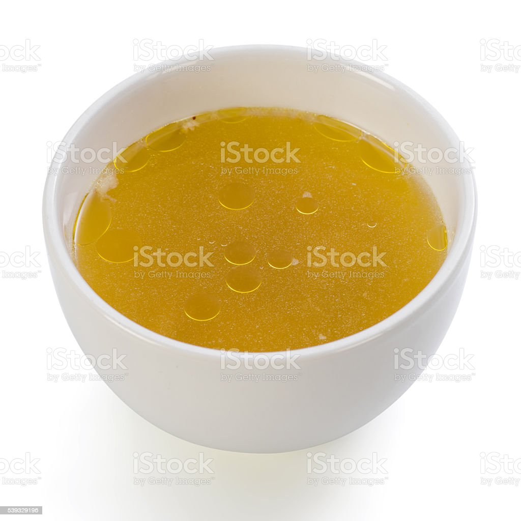Bowl of clear chicken broth stock photo