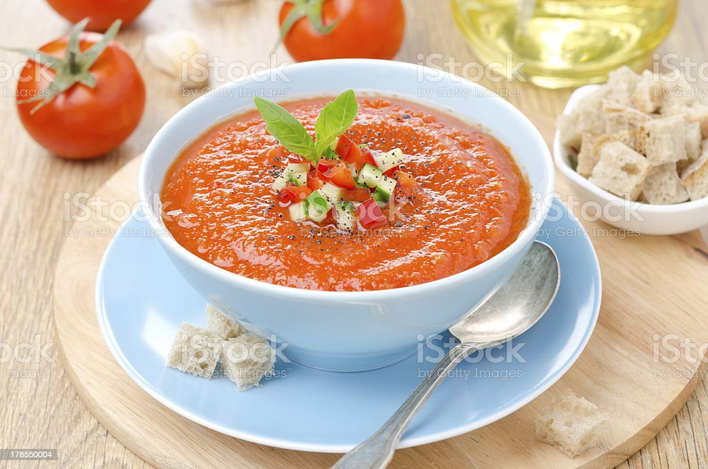 Bowl of cold tomato gazpacho soup with basil and croutons stock photo